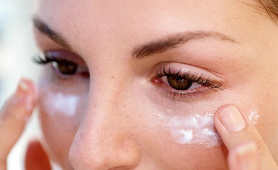 Женщина мажет кожу под глазами